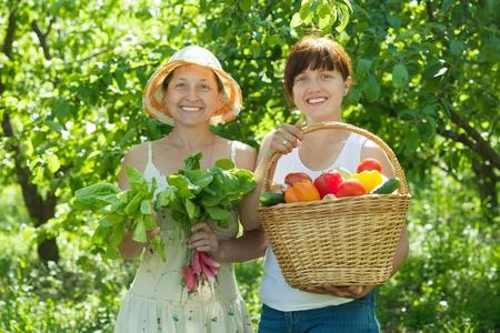 Two happy women with vegetables harvest in garden photo