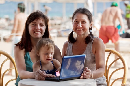 happy family  with laptop  at resort  beach Stock Photo - 12289322