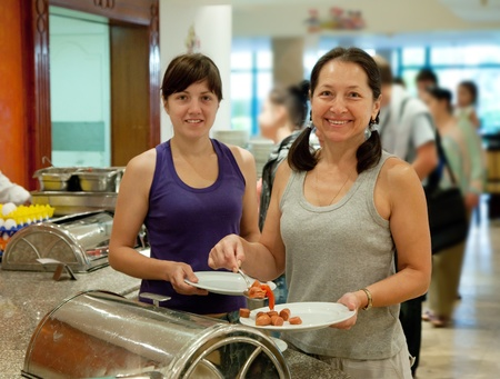 Two women  takes sausages on the buffet table