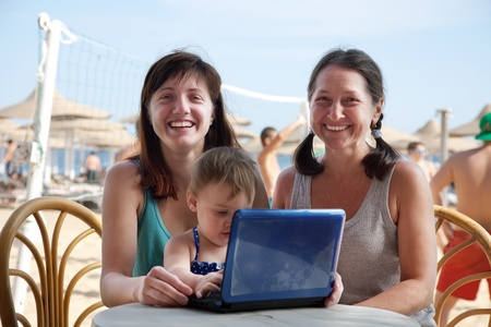 happy women and  girl   with laptop   at resort beach photo