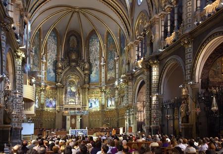 worshipers: SANTA MARIA DE MONTSERRAT, SPAIN - 9 APRIL: Worshipers during worship in catholic church on April 9, Montserrat mountain, Spain. Santa Maria de Montserrat is  greatest monastery of Catalonia