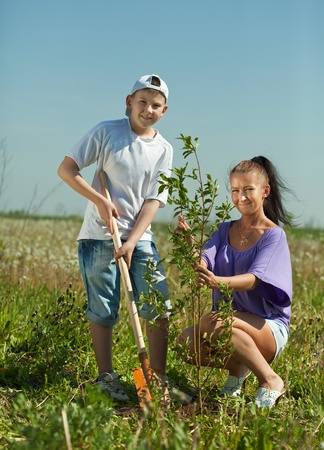 planting season: Mid adult woman with  teenager son setting tree outdoor