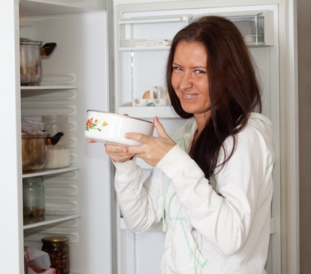 woman  holding foul food  near refrigerator  at home Stock Photo - 12289299