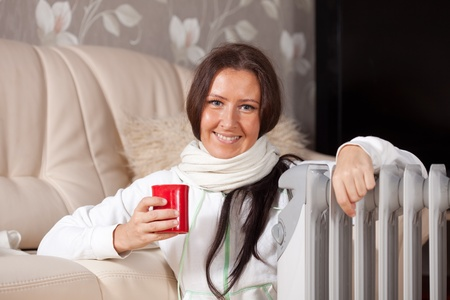 and heating:  smiling woman  with red cup near oil heater