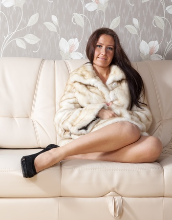 furskin: woman in fur coat sits on sofa at home