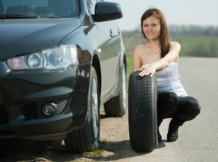 Woman changing car wheel at road photo
