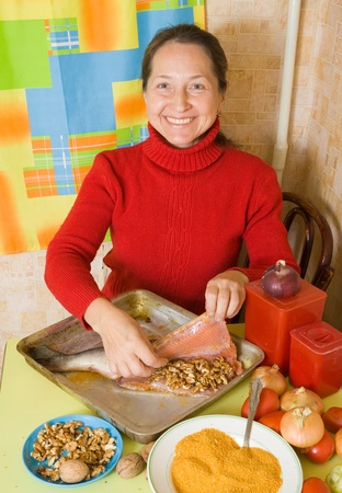 red fish: senior woman is stuffing red fish by walnut