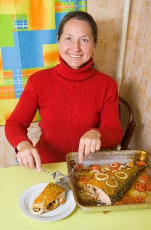 bakplaat: Rijpe vrouw snijden gevulde vis in koken bakplaat