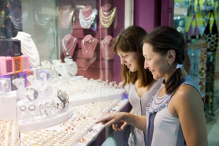 Two women chooses jewelry at shop