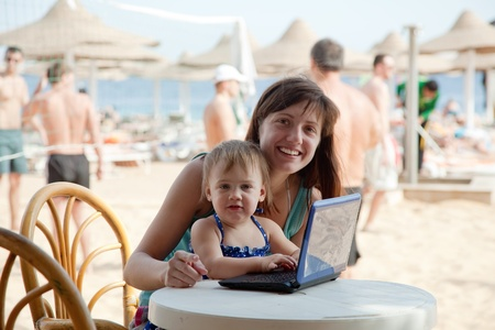 happy mother and  toddler  sitting  with laptop at resort beach photo