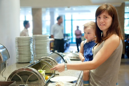 Mother with child  takes the meal  in hotel buffet