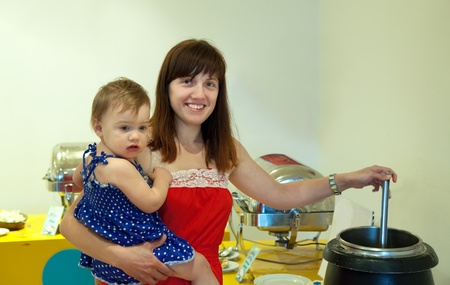 Woman with child  pouring the soup in hotel buffet photo