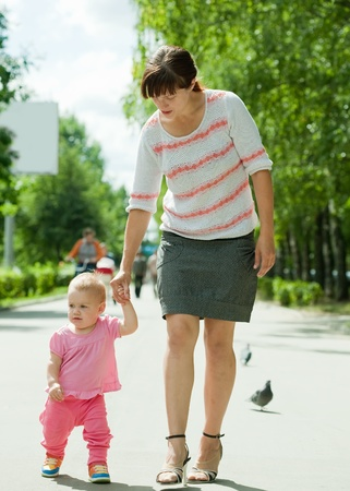 toddler walking: young mother with adorable toddler walking on road
