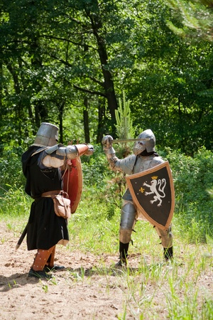 duelling: Two knights in armor is fighting  at forest Stock Photo
