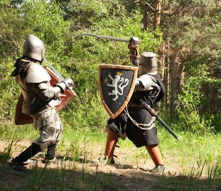 Due cavalieri in armatura sta combattendo in foresta