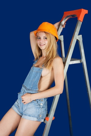 Sexy  female  builder  on scaling-ladder over blue photo