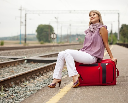 woman with luggage waiting on train photo