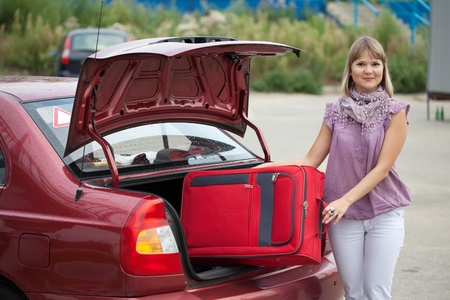 The girl puts the suitcase in the trunk of car photo