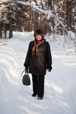 Happy mature woman is walking at winter forest