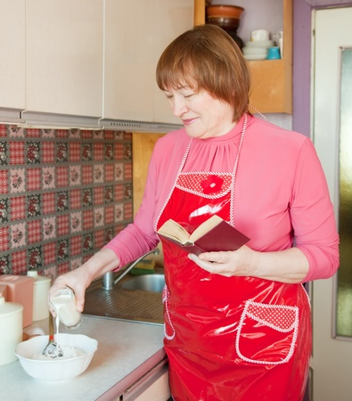 Woman making dough with cookbook in the kitchen photo