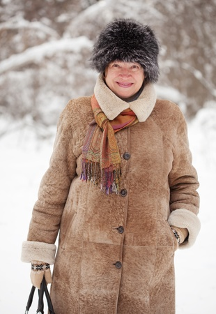 Outdoor winter portrait of mature woman in wintry forest