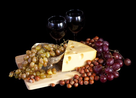 Grapes and cheese with nuts over black background photo