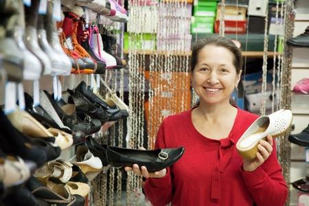 Mature woman chooses shoes at fashionable shop