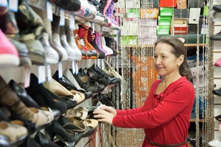 Mature woman chooses shoes at shoes shop