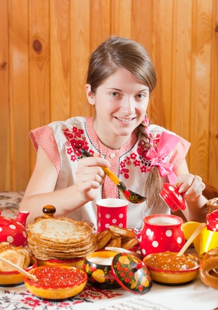Girl in traditional  clothes eating pancake during  Shrovetide photo
