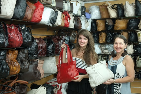 Two women chooses leather bag at  shop