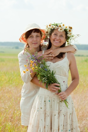 douther: Happy  mature woman wirh adult douther in summer field Stock Photo