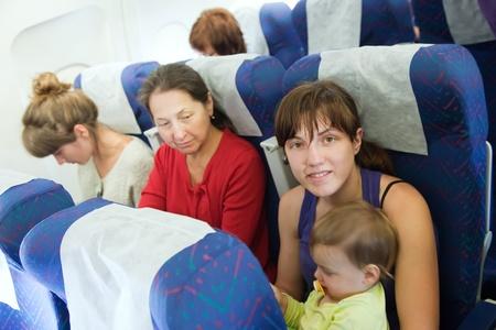 las mujeres con niño en la cabina del avión Foto de archivo