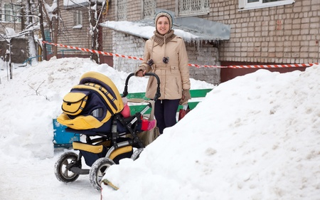 Young woman with pram in winter   photo