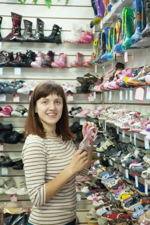woman chooses baby shoes at fashionable shop