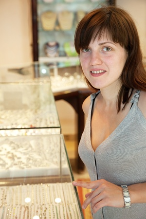 woman  chooses jewelry at   shop