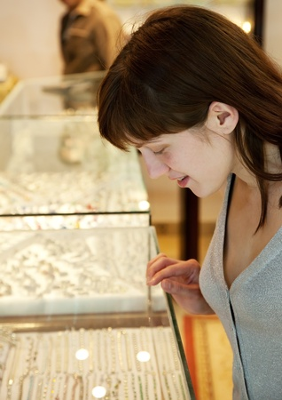 14k: woman  chooses jewelry at   shop