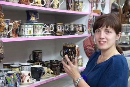 Female tourist  chooses souvenir cup in egyptian shop