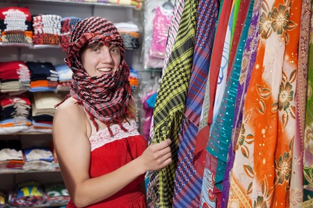 sudarium: woman  chooses  egyptian shawl at  shop