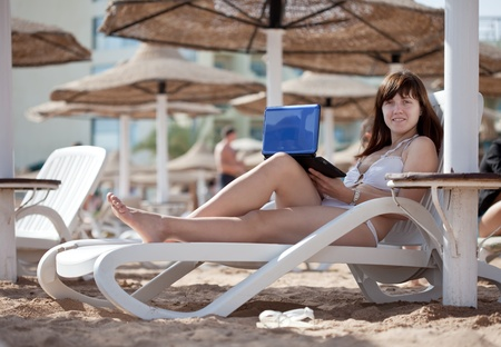 Young woman using  laptop at resort beach photo
