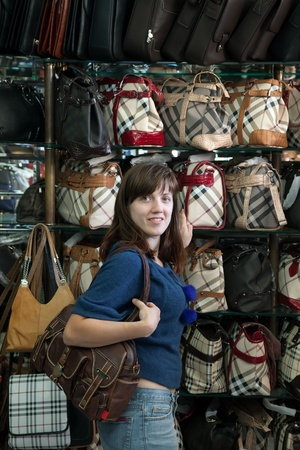 Young woman chooses bag at  shop Stock Photo - 12271323