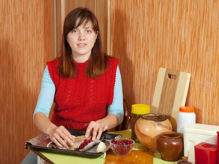 farcie: woman cooking the mackerel with cranberries in the kitchen