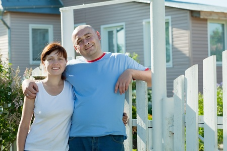 poling:  happy couple posing in front of his  home
