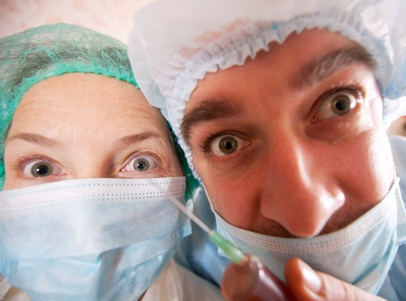 anesthetize: wide angle shot of two   doctors with syringe  Stock Photo