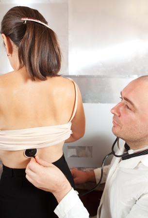 Male doctor examining the patient in clinic photo