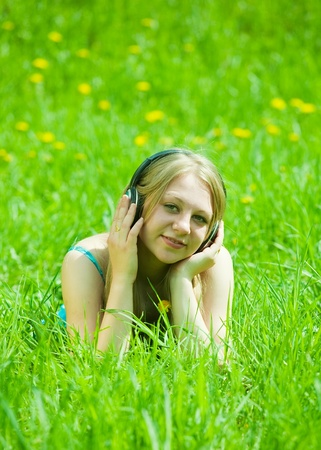Young beautiful happy girl listening music in headphones  outdoor photo