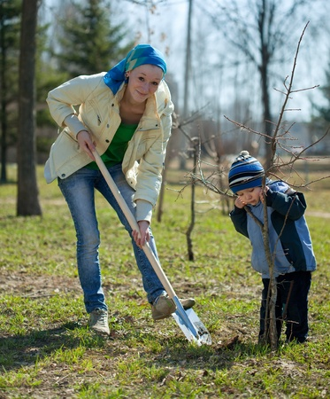 young woman with her son resetting  tree in park  photo