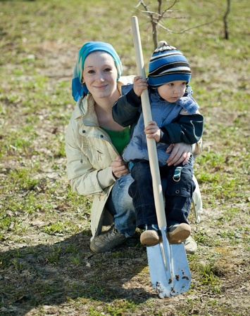 young woman with her son working with spade in orchard  photo