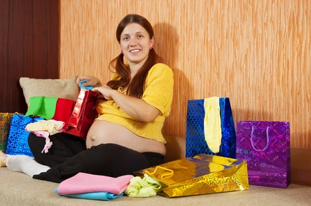 babygro: pregnant woman with purchases  on sofa at home