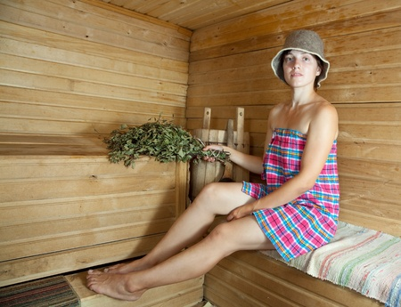 stive: Dressed woman sitting on wooden bench in sauna