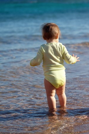 Rear view toddler  in sea wave photo